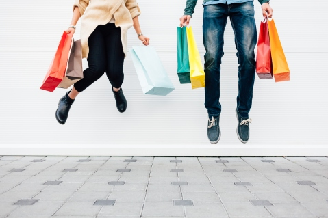 Couple jumping with shopping bags